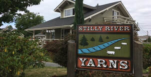 Photo of Stilly River Yarns logo sign and the shop building